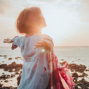Foto de mulher numa praia com sensação de liberdade - Coaching Transformacional