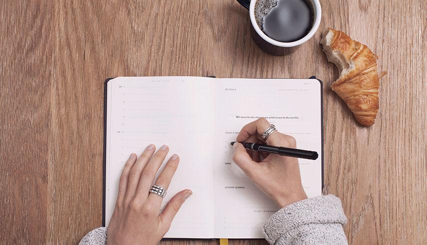 Imagem de uma mulher a definir objetivos para o novo ano e a escrevê-los num planner