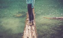 Foto de mulher a equilibrar-se num tronco na água