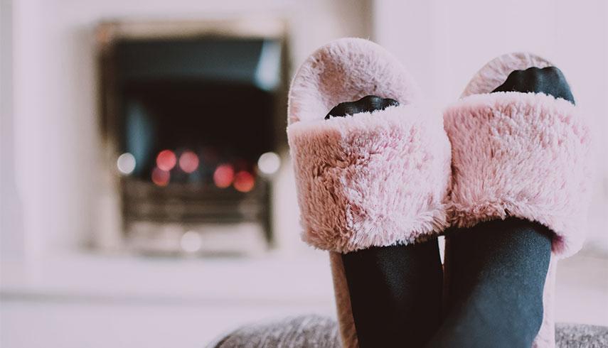 Imagem de uma mulher com pantufas, deitada no sofá perto da lareira
